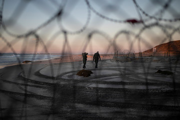U.S. Customs and Border Protection (CBP) officials walk on the beach in San Diego County, U.S., as photographed through the border wall in Tijuana