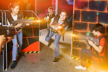 Group of happy teenagers with laser guns having fun on dark lase