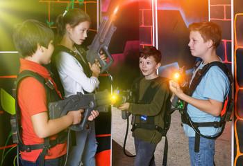 Joyful teens aiming laser guns at other players