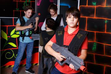 teen boy standing with laser pistol in dark lasertag room
