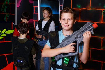 Portrait of preteen boy with laser pistol posing in laser tag la