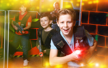 Emotional teen boy with laser pistol playing laser tag with frie
