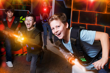 boy aiming laser gun at other players during lasertag game