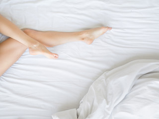 Poster Spa Female legs on the bed. Legs on white sheets. Epilation and health concept.