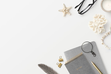 top view / flat lay of a boho styled feminine home office workspace with notebooks, glasses, a feather, corals and other natural decorative elements on a white desk - copyspace for your text