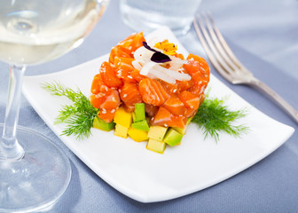 Salmon tartare formed as cube with avocado