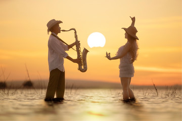 Musicial playing saxophone with sunset background