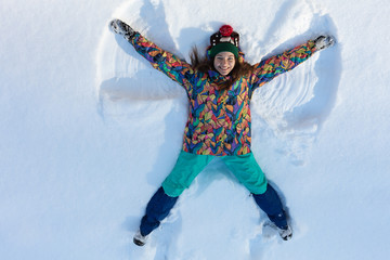 High angle view of happy girl lying on snow and moving her arms and legs up and down creating a snow angel figure. Smiling woman lying on snow in winter holiday with copy space