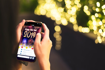 Woman Hand holding mobile see live streaming countdown to Happy new year 2019 with fireworks over cityscape on screen with light bokeh background,Digital social media lifestyle.