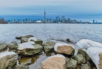 Skyline of Toronto on a cold morning with ice on the foreground