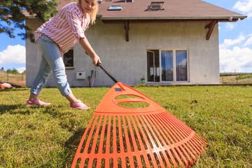 Unusual angle of woman raking leaves