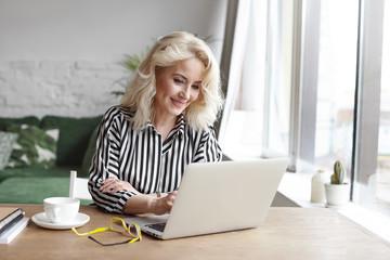 Stylish blonde sixty year old female teacher wearing striped blouse having online class via video chat on laptop pc, sitting at wooden desk in modern interior, smiling joyfully, enjoying communication
