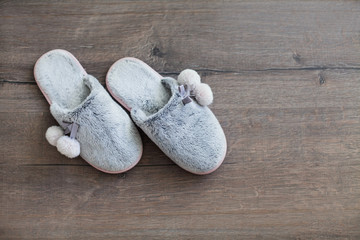 fur slippers on a dark wooden background