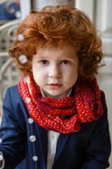 portrait of a stylish little boy with red hair