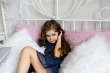 cute little girl is sitting on the bed
