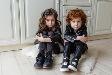 trend boy and girl are sitting on the floor in black leather clothes. stylish brother and sister in leather black jackets sit on the kitchen floor
