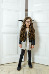 little fashionable girl with glasses posing on the door background