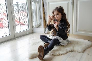 little stylish girl doing selfie on phone on floor in kitchen