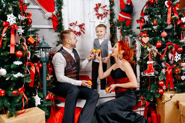 A young family sitting on the floor near a Christmas tree and juggling mandarins