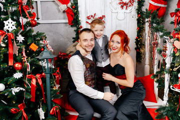 A young family stands and smiles near the Christmas trees in New Year costumes