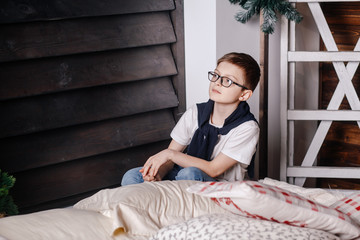 A boy in glasses sits and looks out the window