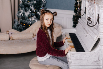 Little girl playing on white piano
