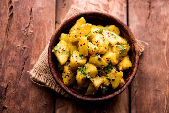 Jeera Aloo is a Indian main course dish which goes well with hot puris, chapatti, roti or dal. served in a bowl over moody background. selective focus