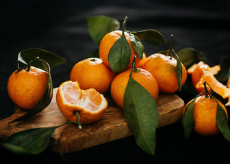 Ripe mandarins with leaves on a black background