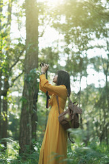 Attractive Asian woman adventure in the forest sightseeing natural and using camera take a photo at holiday travel concept.
