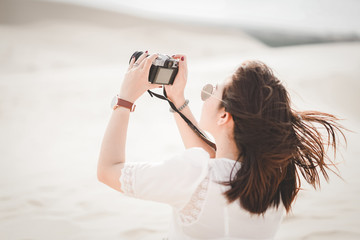 Traveling and photography. Young woman with camera taking photo at White Sand Dunes, Vietnam.