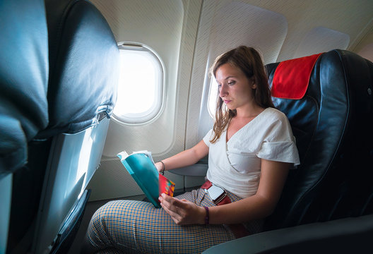 girl reading a book in the airplane during flight