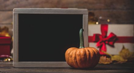 leaves and pumpkin with Halloween gift box and blackboard on Fairy Ligths background. Autumn season image composition