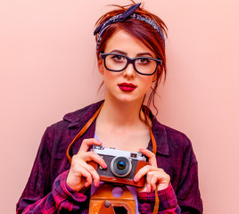 Young redhead girl in bandana holding vintage camera at pink background