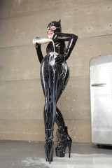 hungry cat woman with mask helmet with a bottle of milk pours it over a black latex catsuit on a silver fridge background in her grey loft apartment