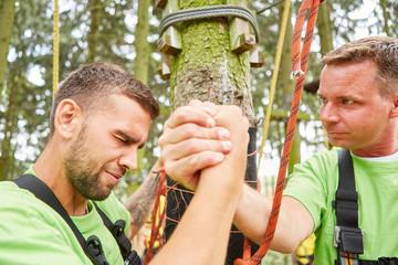 Männer im Hochseilgarten feiern ihren Erfolg