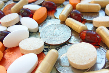 Pills, tablets and capsules with American coins on dollar usa background. Pharmacy and money theme, health care, drug prescription for treatment medication