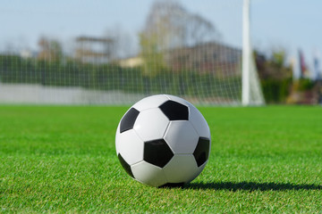 Classic soccer ball lies on the bright green grass on the football field against the background of the stands for fans and the football goal at a sports stadium close-up in a large sports center