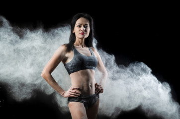 Graceful woman posing in a cloud of dust on a black background