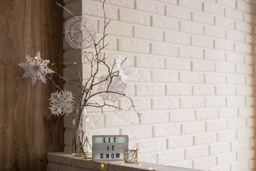 Let it snow it is written on a decorative lamp next to a home winter decor with a vase with tree...