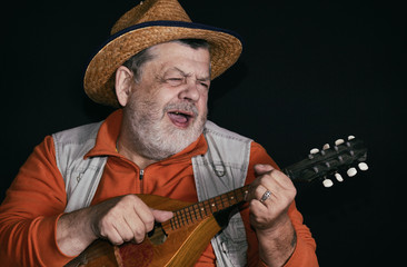 Nice low key portrait of senior musician with mandolin playing and singing country music