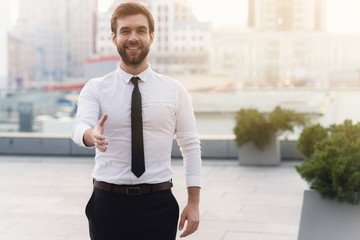 Young handsome man businessman in a white shirt and necktie is smiling joyfully against the background of the city on a sunny day giving a hand for a greeting.