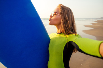 beautiful and young smiling surfer girl in a diving suit wetsuit holding surfboard and photographing a selfie portrait on smartphone summer sunset on the beach.