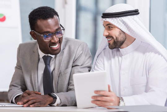 Multicultural business partners looking at digital tablet in modern office