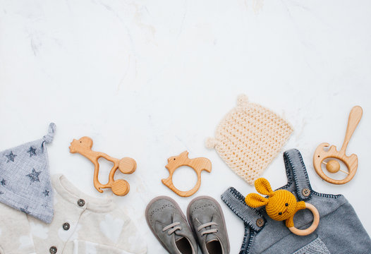 Newborn baby clothing, shoes and toys on light marble background