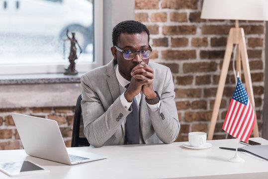 African american businessman sitting at desk modern office