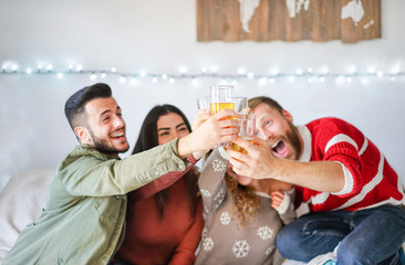 Group of friends cheering with beer at home christmas party