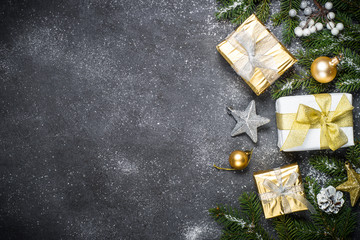 Christmas background with gold and silver decorations on black.