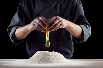 Falling eggs into flour. Hands breaking cracking a raw egg over flour, baking concept. Baker kneads the dough for the pasta. The process of breaking eggs.
