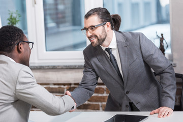 smiling multiethnic business partners shaking hands at office table