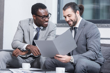 multiethnic businessmen smiling and reading document in office
